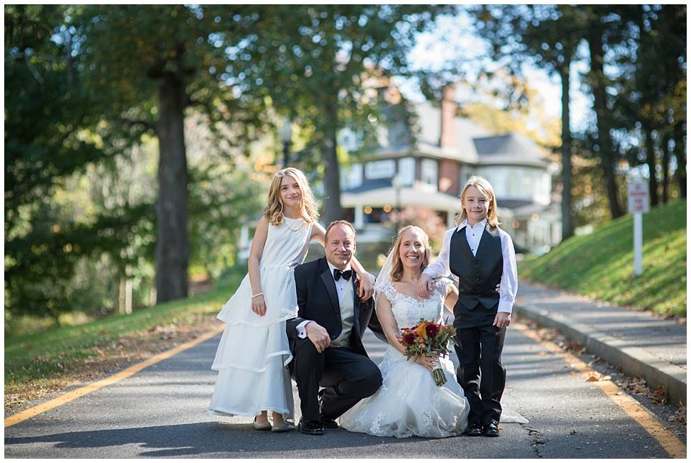 bride, groom and kids in front of mansion