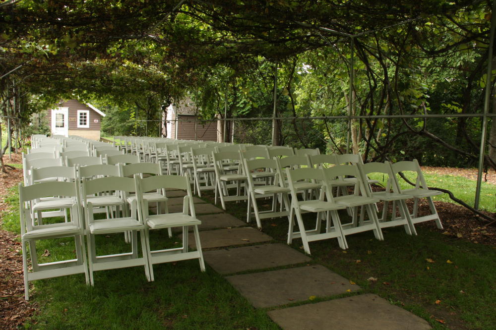 white chairs set up under the grape arbor for ceremony