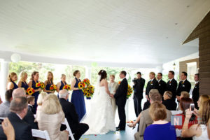 bride and groom exchanging vows in front of guests on veranda