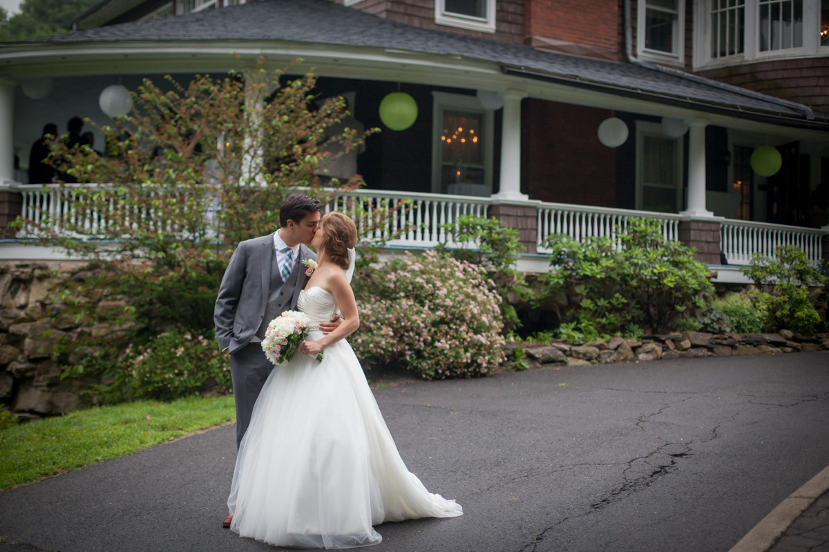 bride and groom kissing in front of the decorated veranda