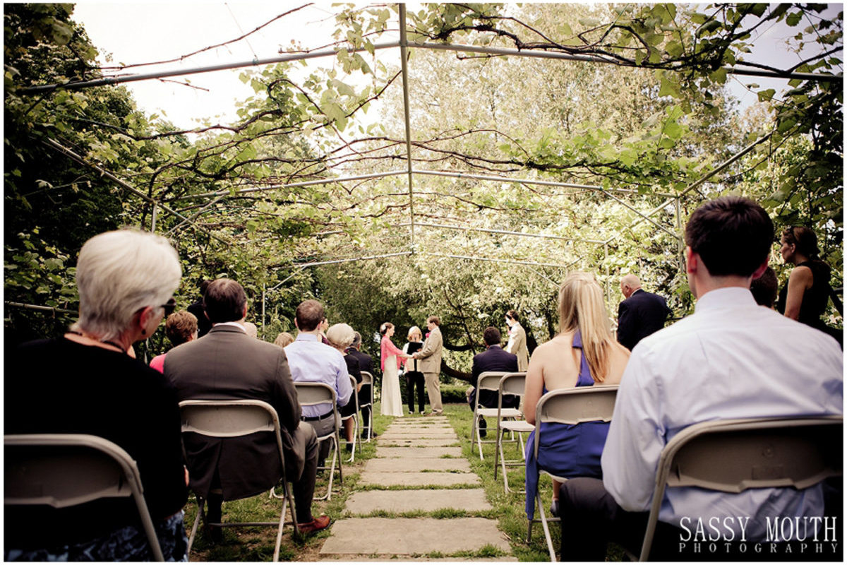 wedding ceremony under the grape arbor with guests seated looking on