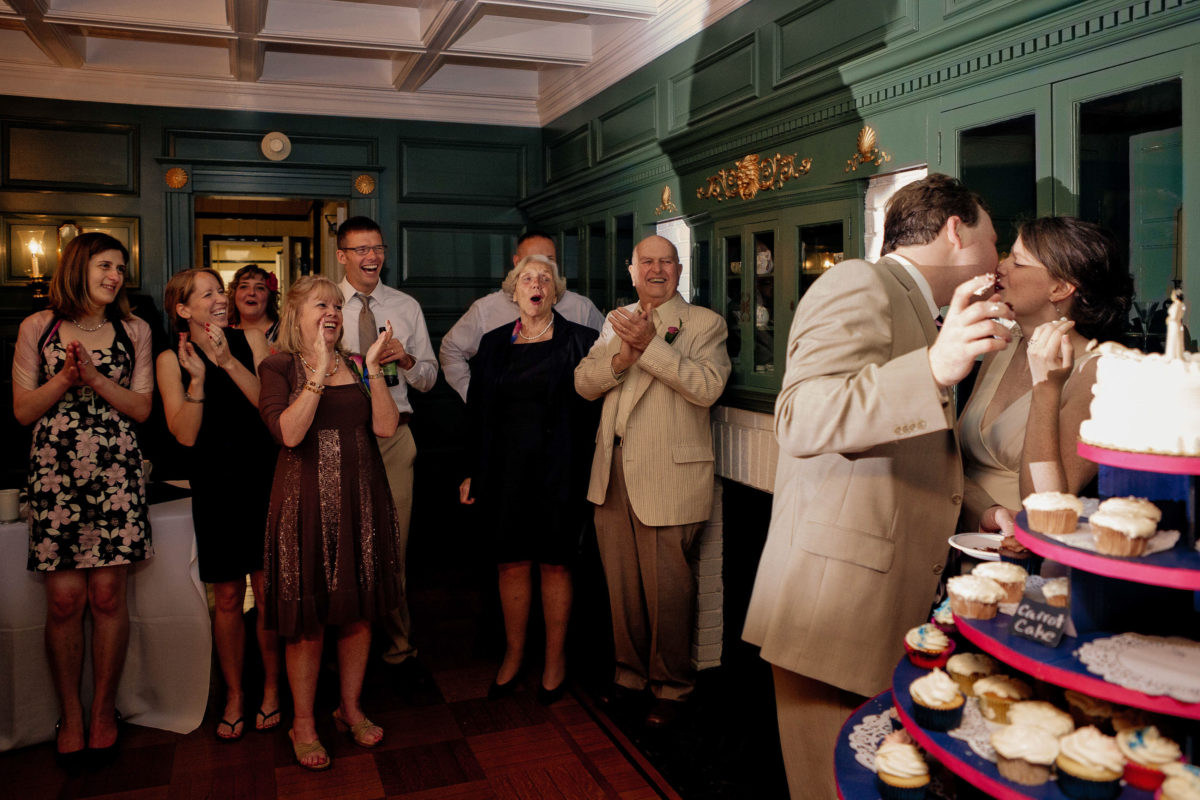 groom kises bride with frosting lips while guests clap