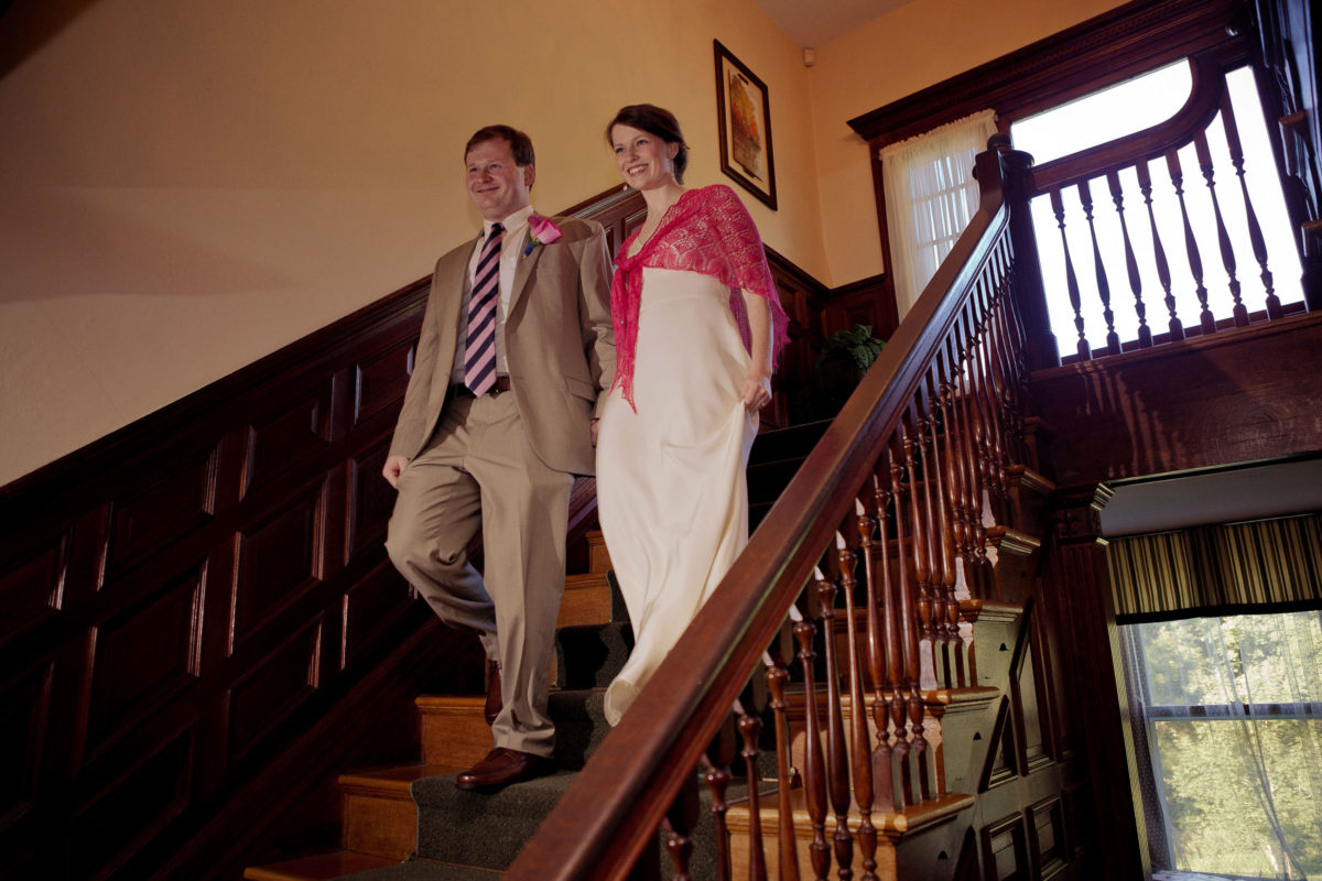 couple coming down staircase to reception as man and wife