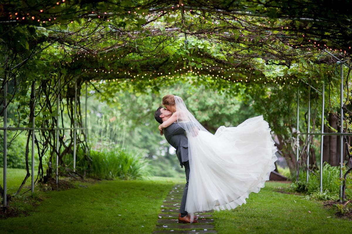 high-school-sweethearts-wed-groom-lifting-bride-in-a-kiss