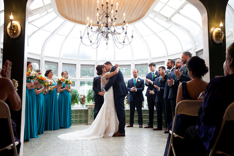 couple kissing after ceremony with wedding party clapping