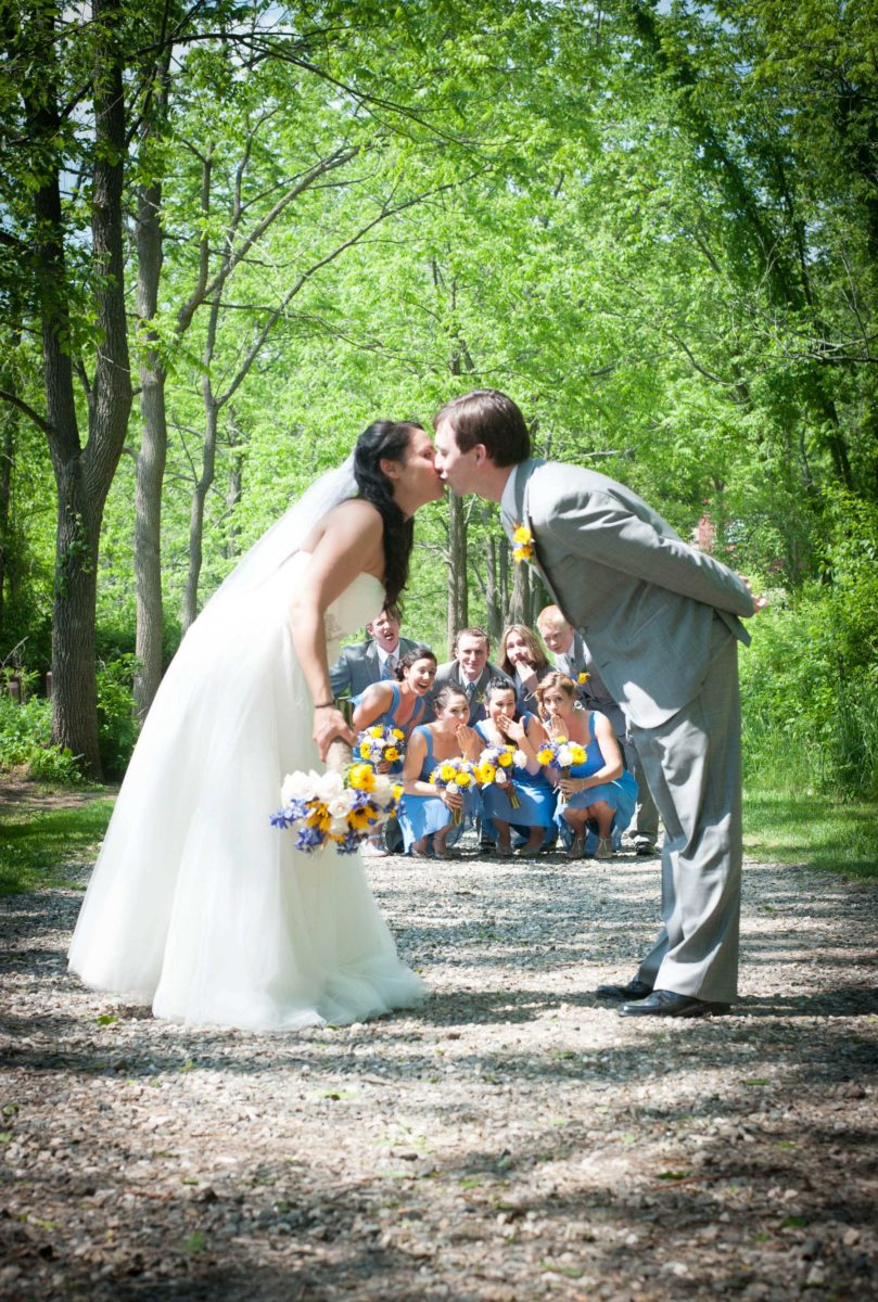 couple kissing while bridal party looks on