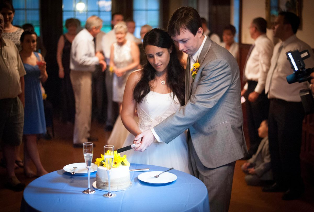 couple holding the knofe to cut the cake