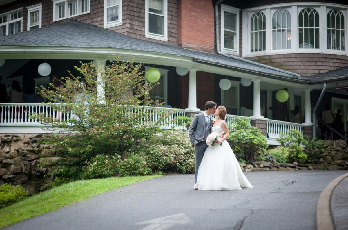 bride and groom kissing in front of decoraged mansion