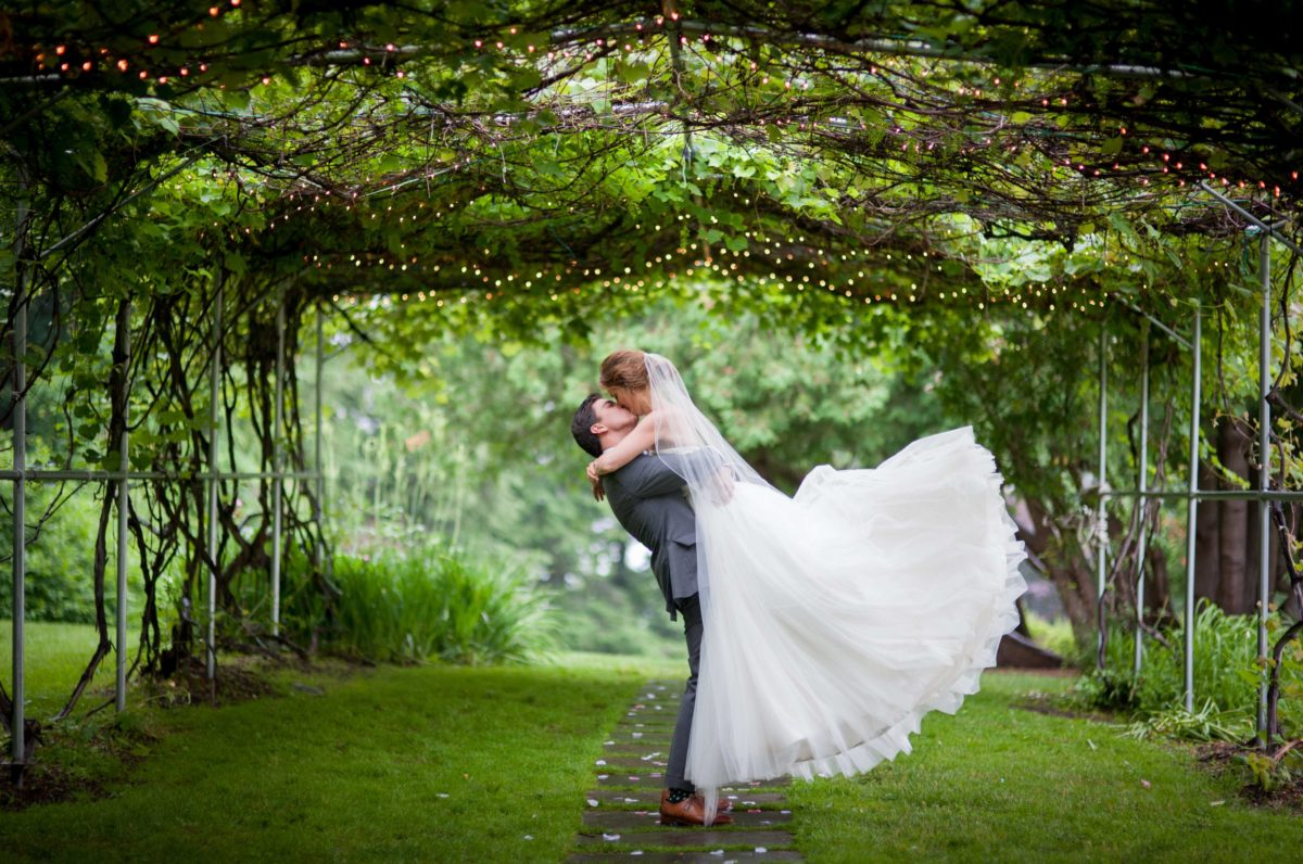 groom lifting up bride for kiss under the grape arbor