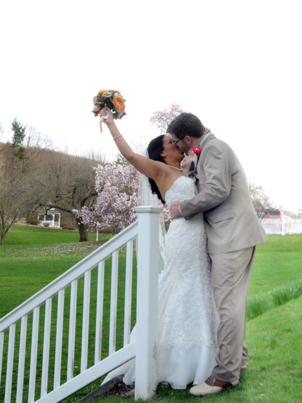 bride and groom kissing in front of magnolia tree