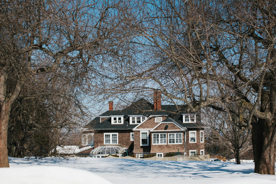 view of mansion across snow laden lawn