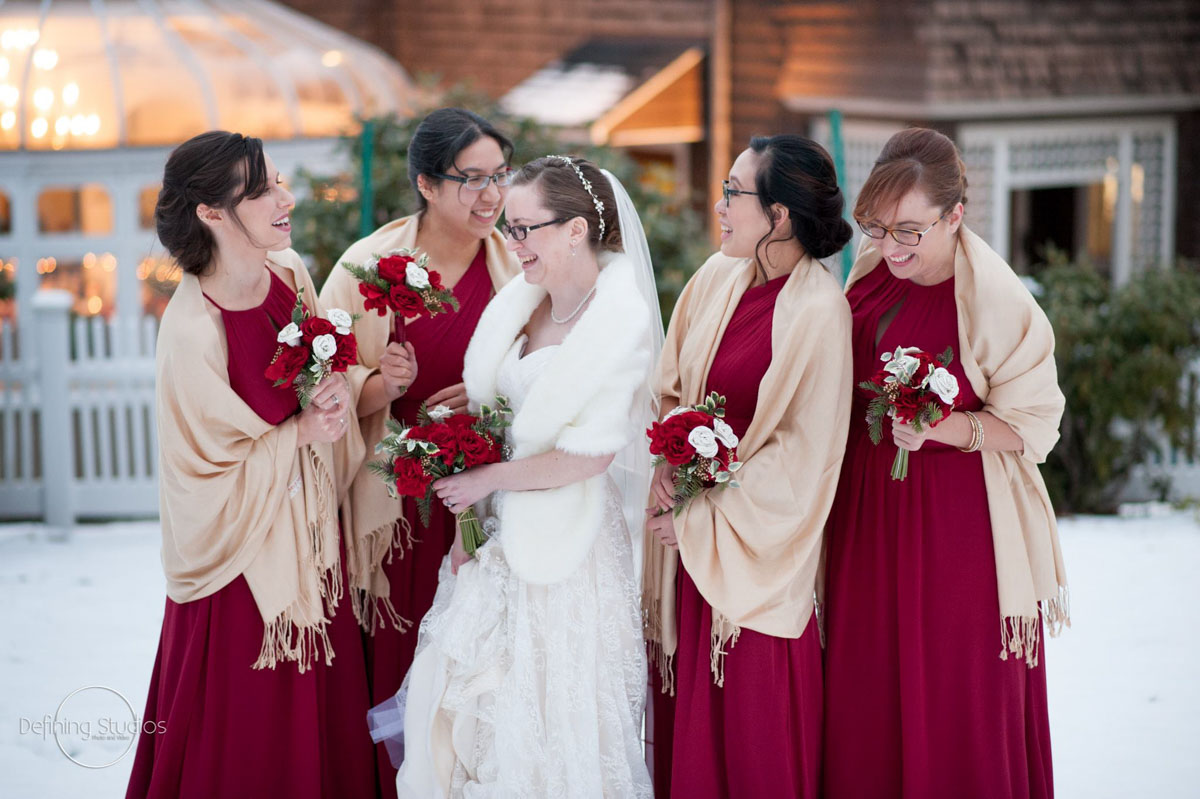bride and her bridesmaids laughing outside in the snow
