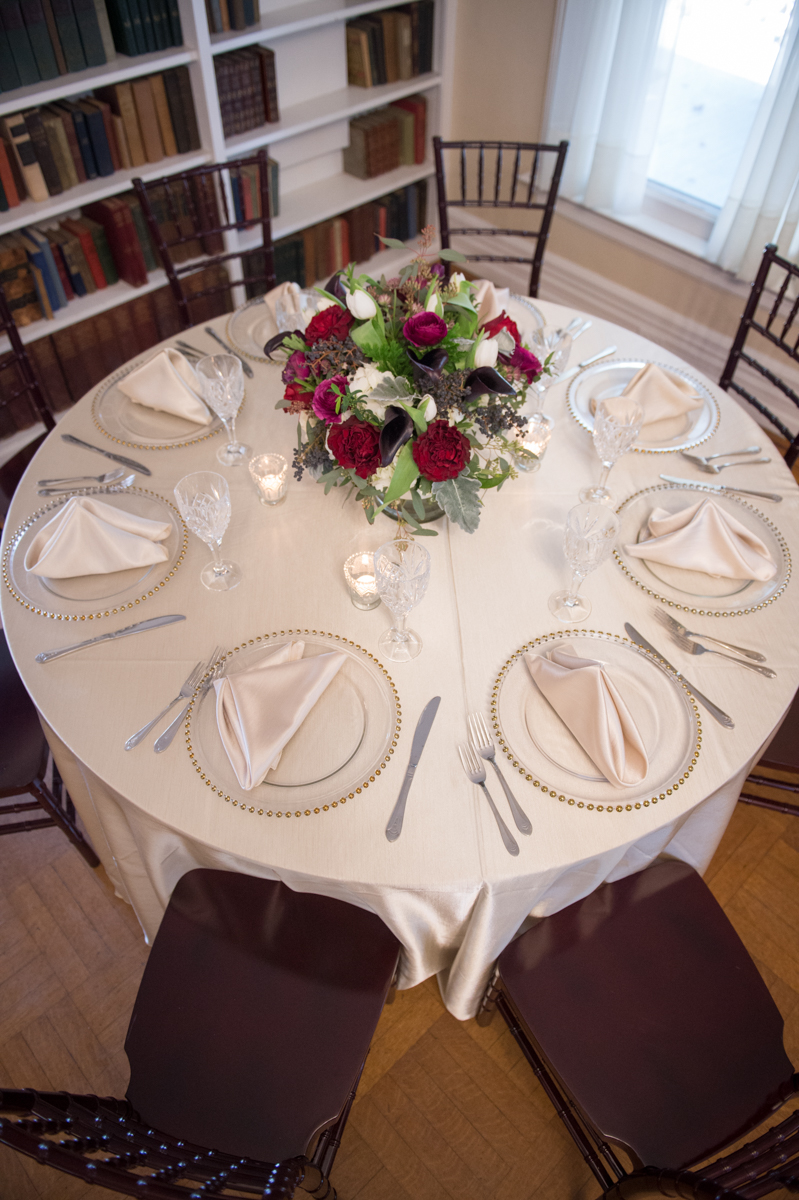 Clear charger plates with white linen tablecloth, add a bold red centerpiece