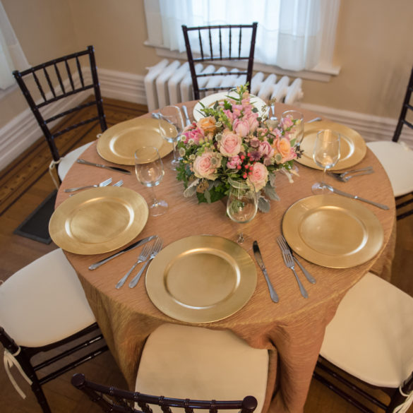 gold plates on round table with flowers