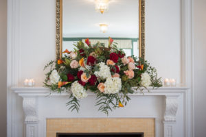 large floral arrangement on the fireplace mantle