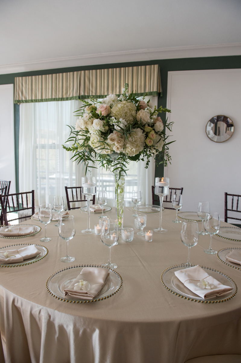 white floralarrangement in long stemmed vase on a table with biege linens