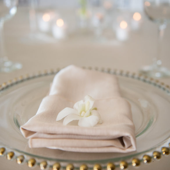 gold rimmed plate with white linen napkin and flower