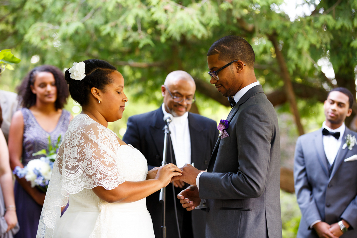 bride places ring on grooms finger during the grape arbor ceremony