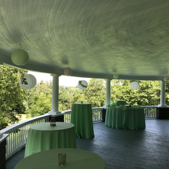 tables set up on veranda with green lanterns and linens