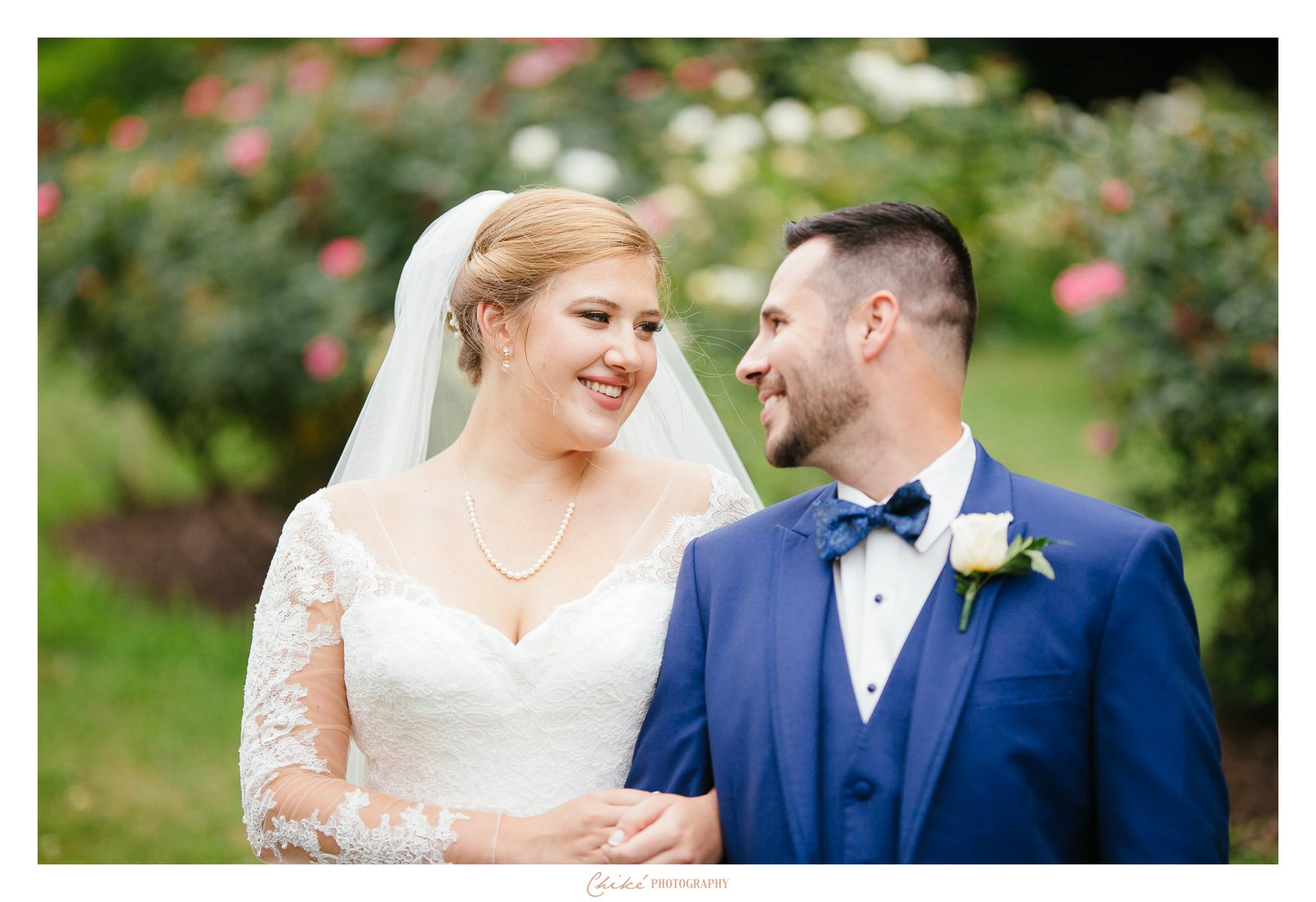 bride and groom looking into each others eyes by the roses