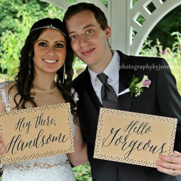couple in gazebo holding signs hey there handsome and hello georgeous
