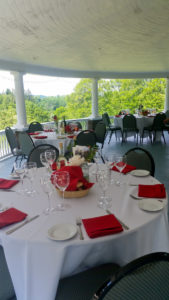 tables set with red and white linens on the veranda