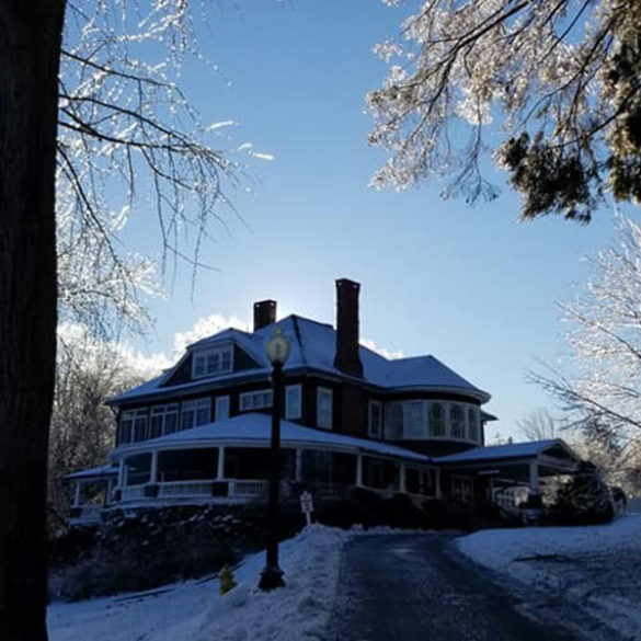 view-of-mansion-from-dirveway-covered-in-ice-and-snow