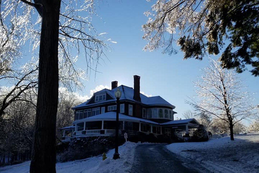 view of mansion from dirveway covered in ice and snow