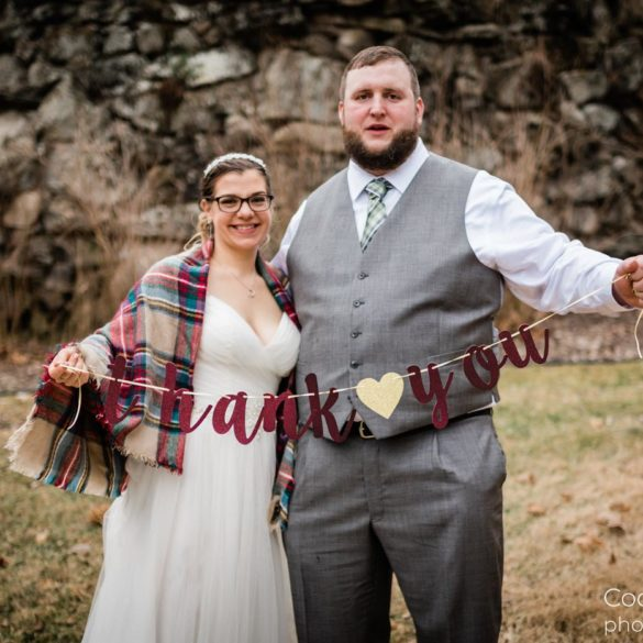 wedding-couple-outside-in-front-of-mansion-with-thank-you-banner