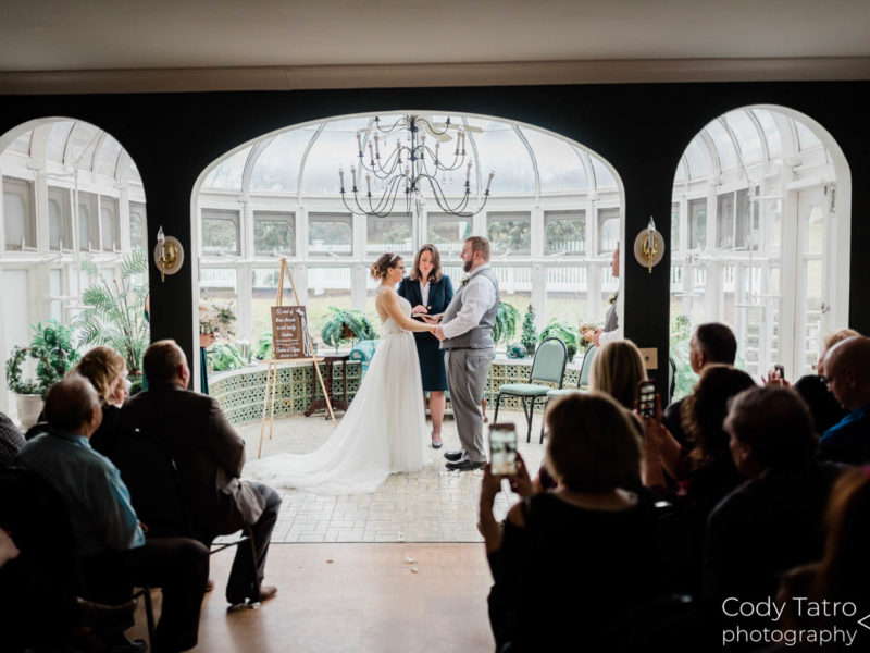 winter wedding ceremony in conservatory couple praying with pastor