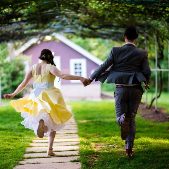 newlyweds-running-hand-in-hand-dow-the-garden-path