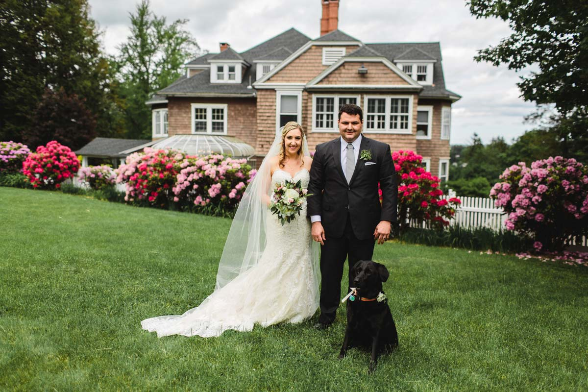 tent-reception-couple-standing-on-lawn-with-black-dog