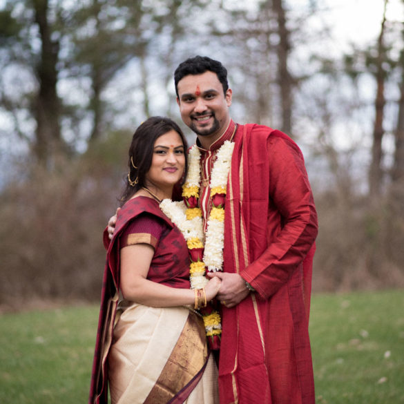 couuple-facing-the-camera-on-lawn-in-their-formal-indian wedding-attire