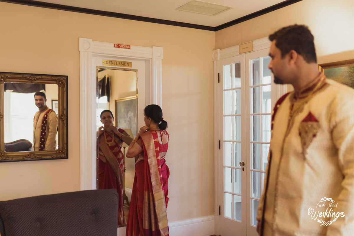 mom-looking-in-mirror-with-groom-looking-on-for_indian-wedding