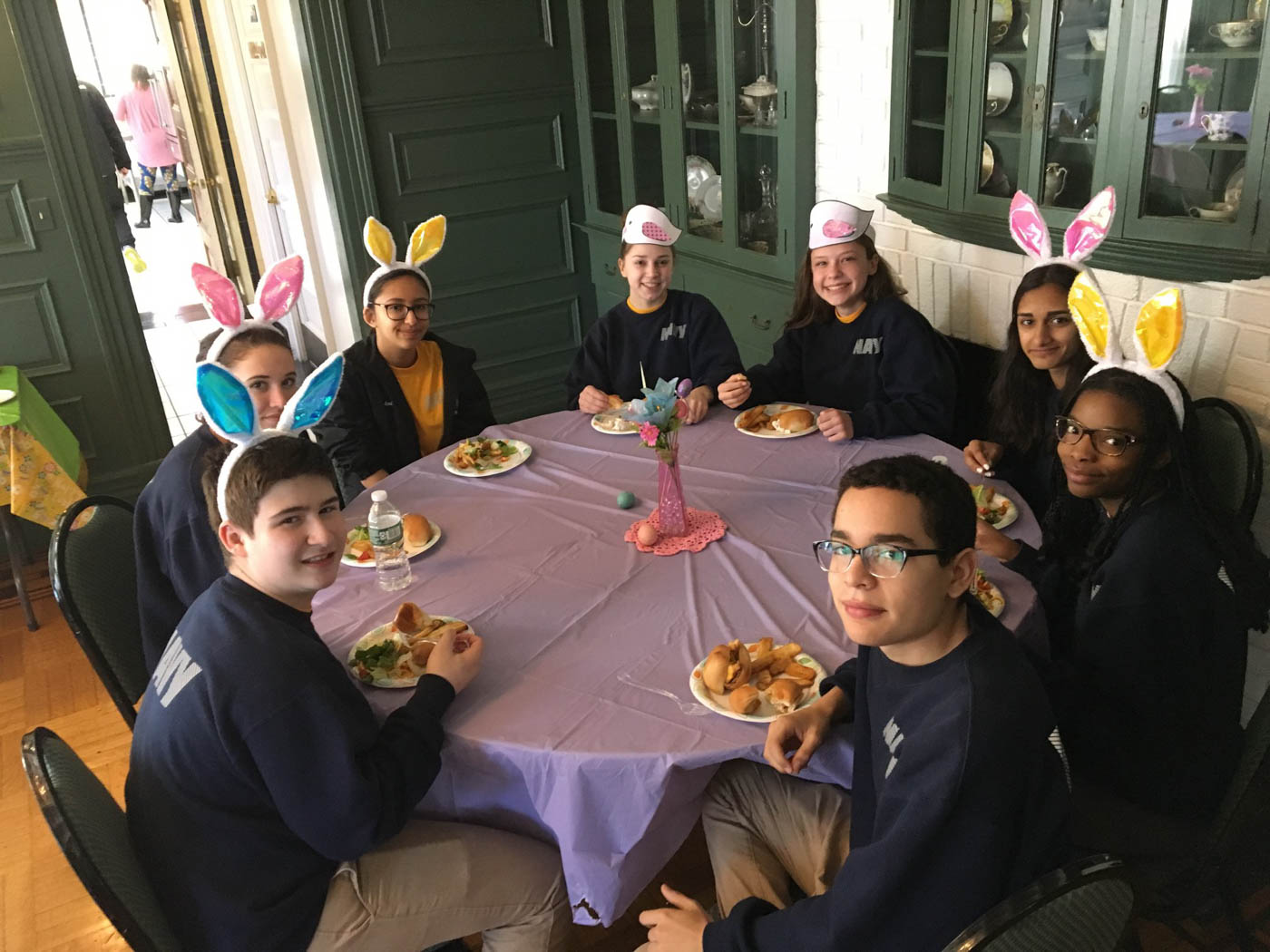 fundraising-volunteers-sitting-around-table-eating-with-bunny-ears-on