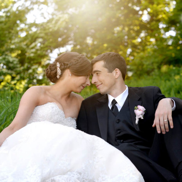 wedding-couple-with-foreheads-together-sitting-in-flower-garden