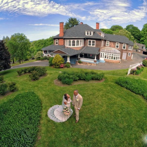 drone shot of couple and mansion rounds
