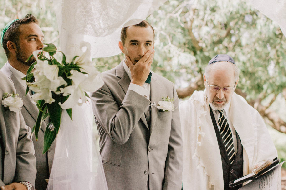 jewish-wedding-ceremony-groom-covers-mouth-in-awe-at-sight-fo-bride