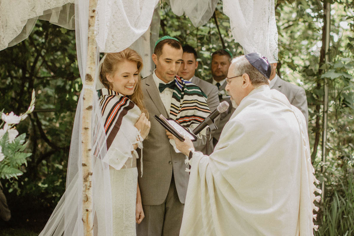 jwish-wedding-ceemony-rabbi-reads-blessings-to-couple-under-chuppah