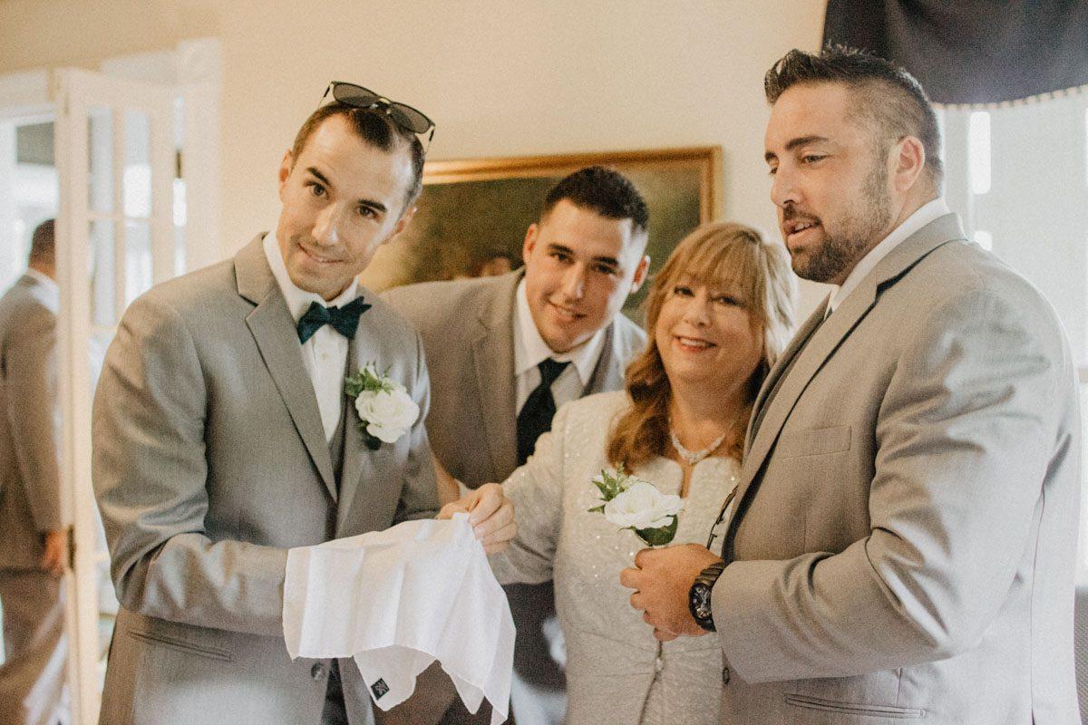 jewish-wedding-ceremony-mom-helping-groom-fold-handkerchief