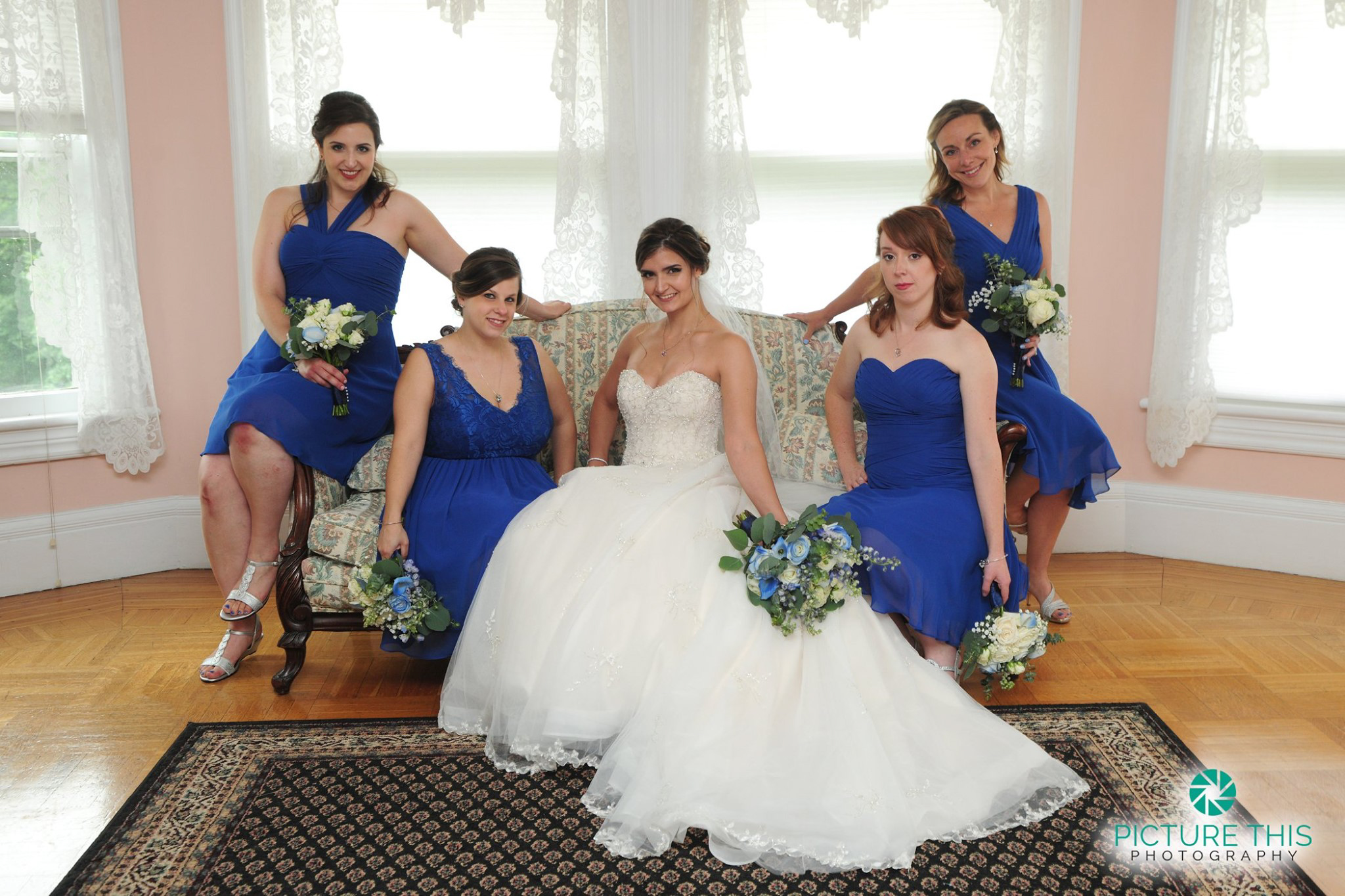 late-june-wedding-party-bride-sitting-with-bridesmaids