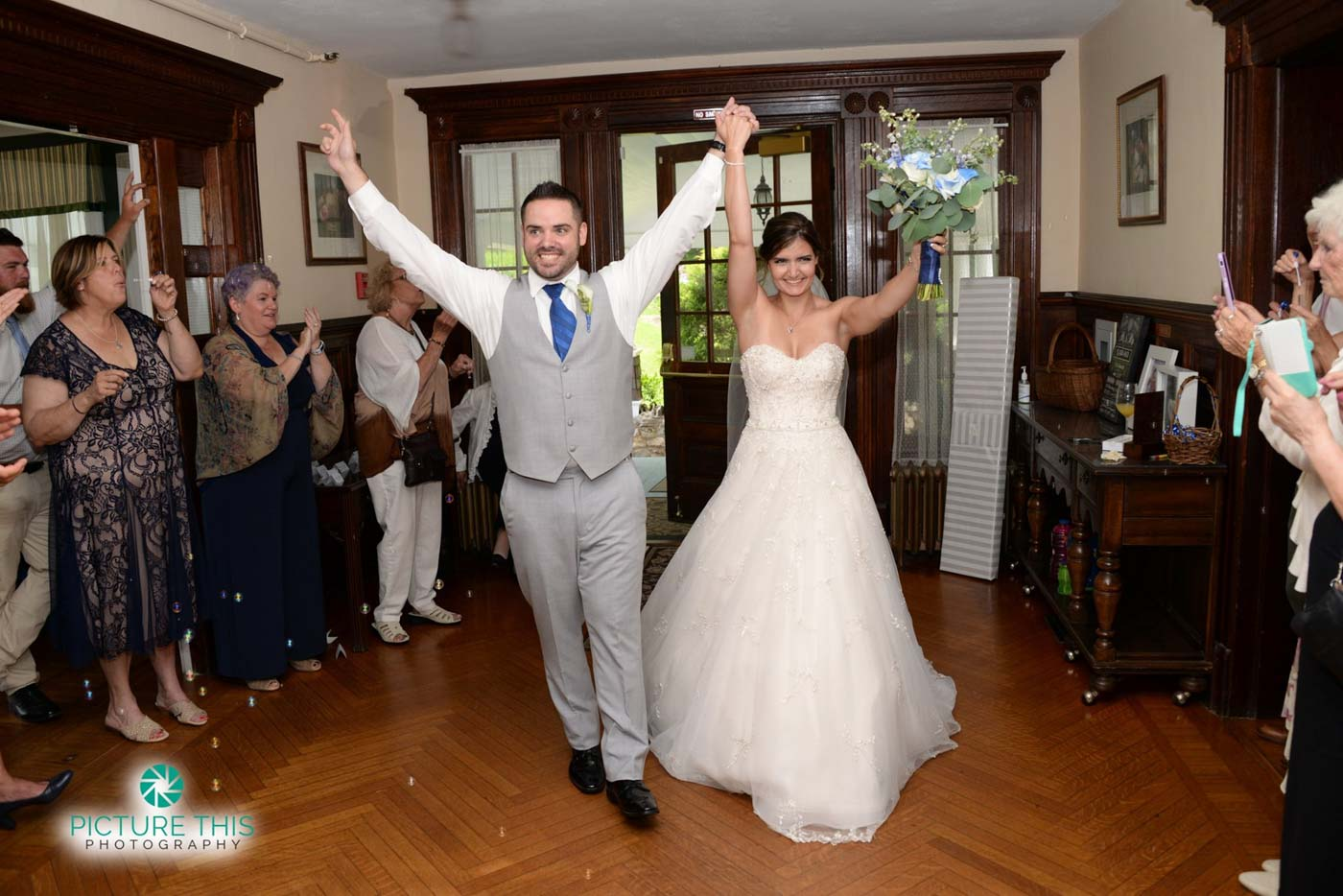 a-late-june-wedding-couple-walking-into-mansion-with-arms-lifted-high