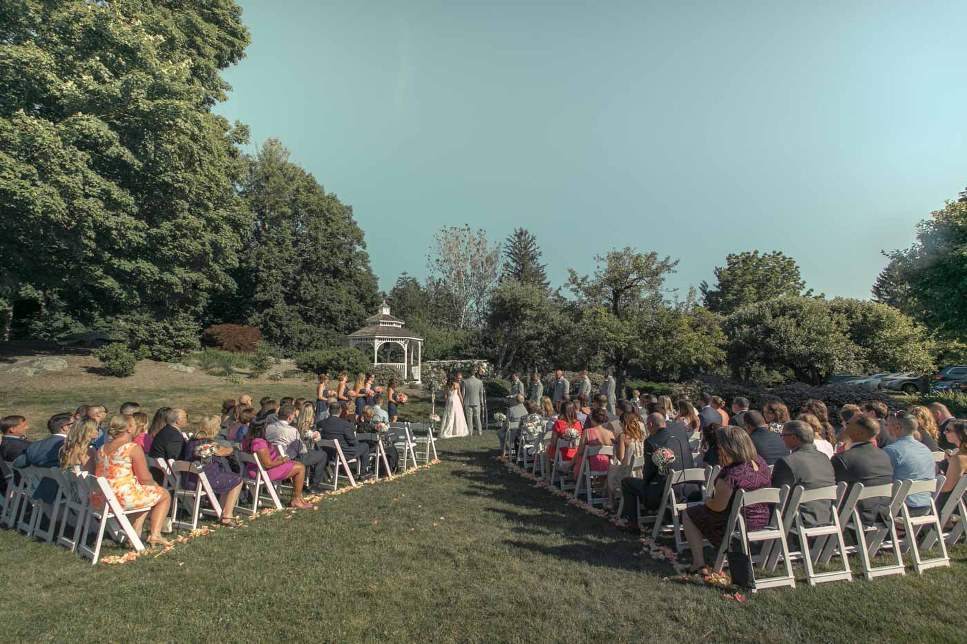 summer-ceremony-guests-seated-on-lawn-gazebo-in-background