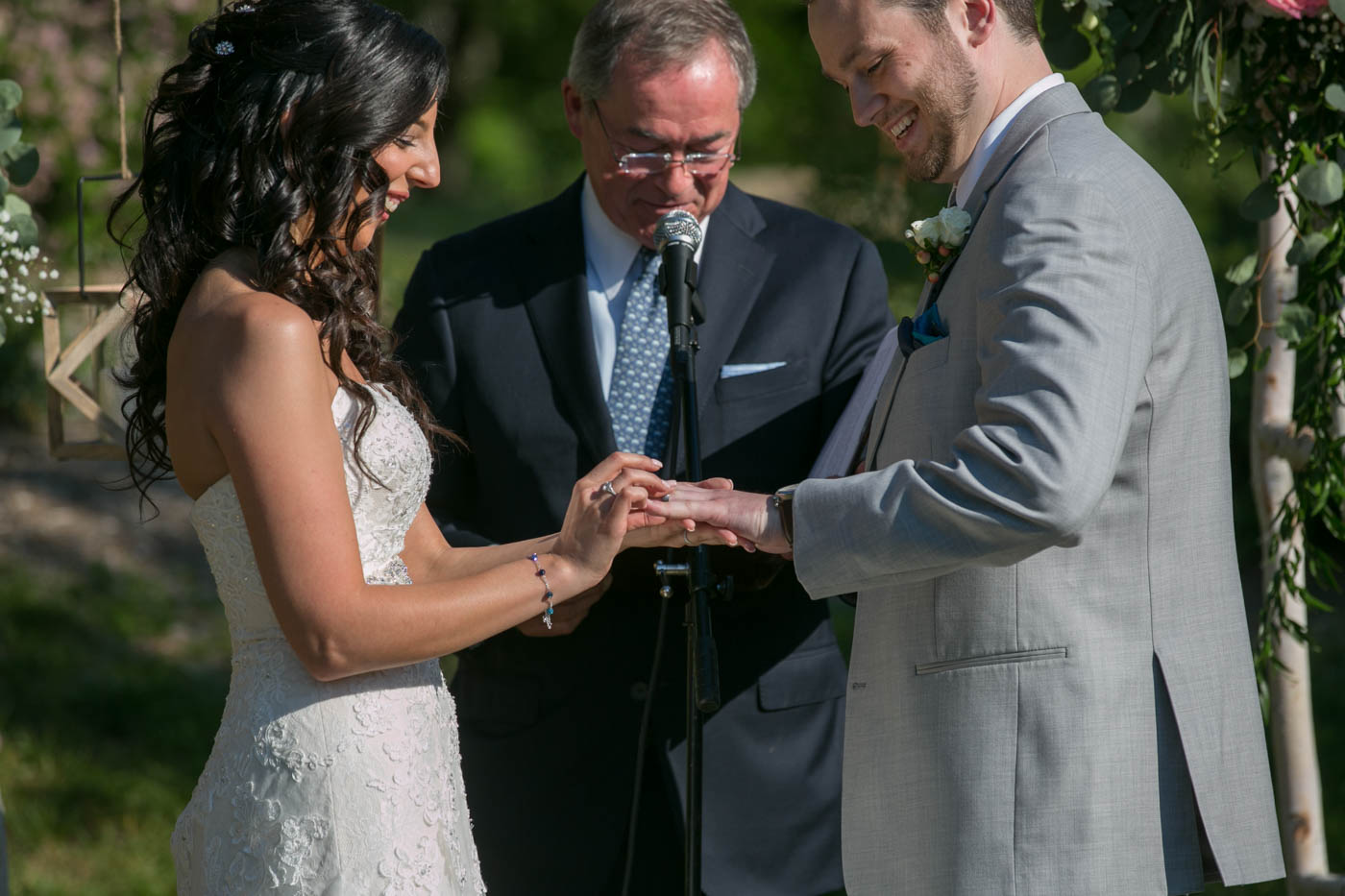 bride-placing-ring-on-grooms-finger-summer-wedding