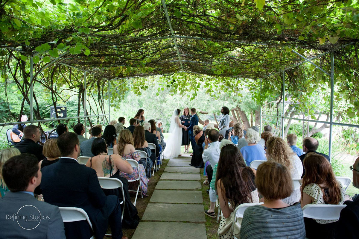 Grape arbor wedding ceremony, exchanging vows.