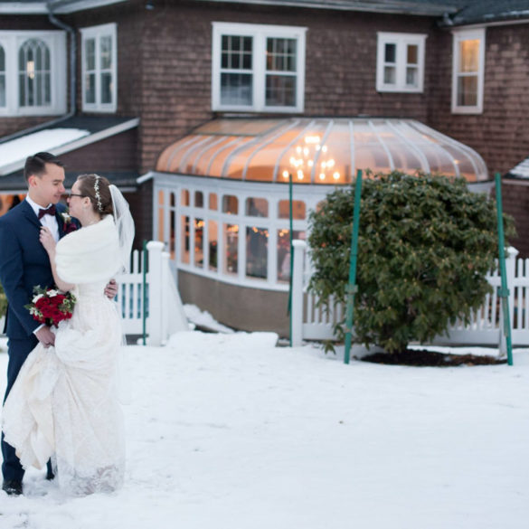christmas-wedding-couple-standing-close-together-with-mansion-as-background