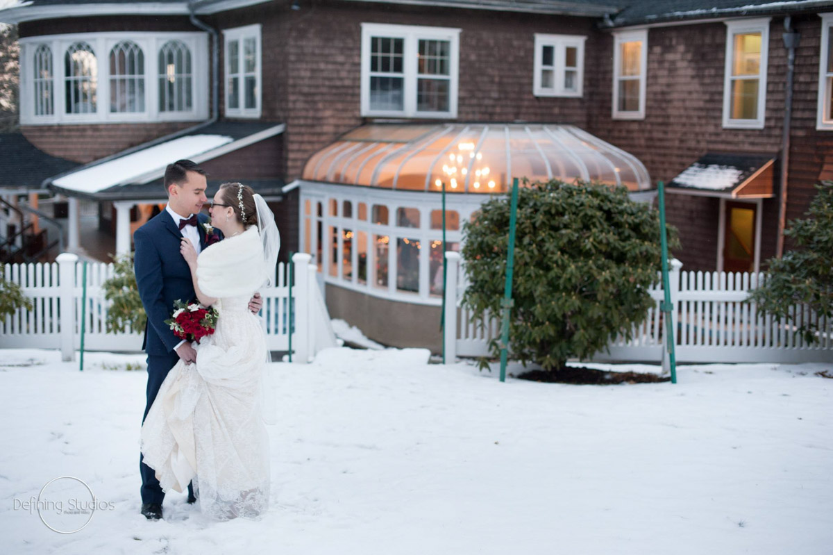 amanda and andy in the snow in front of the mansion