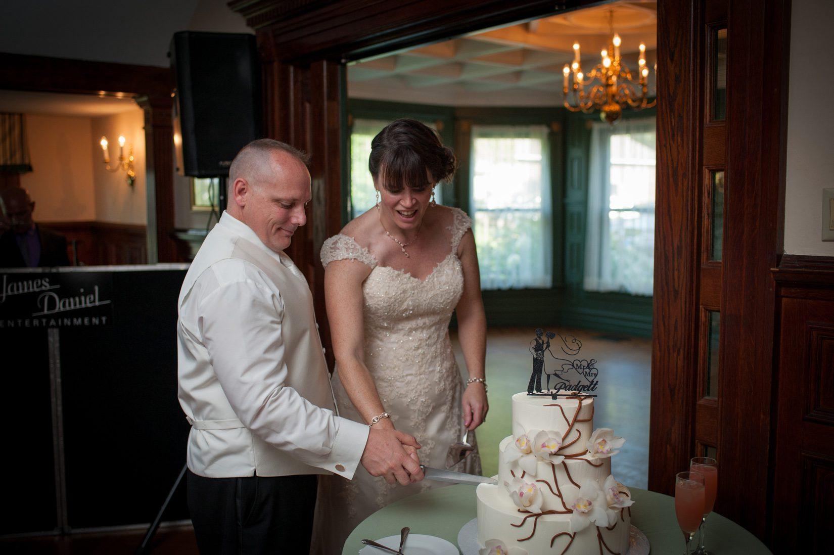 couple cutting three tier cake