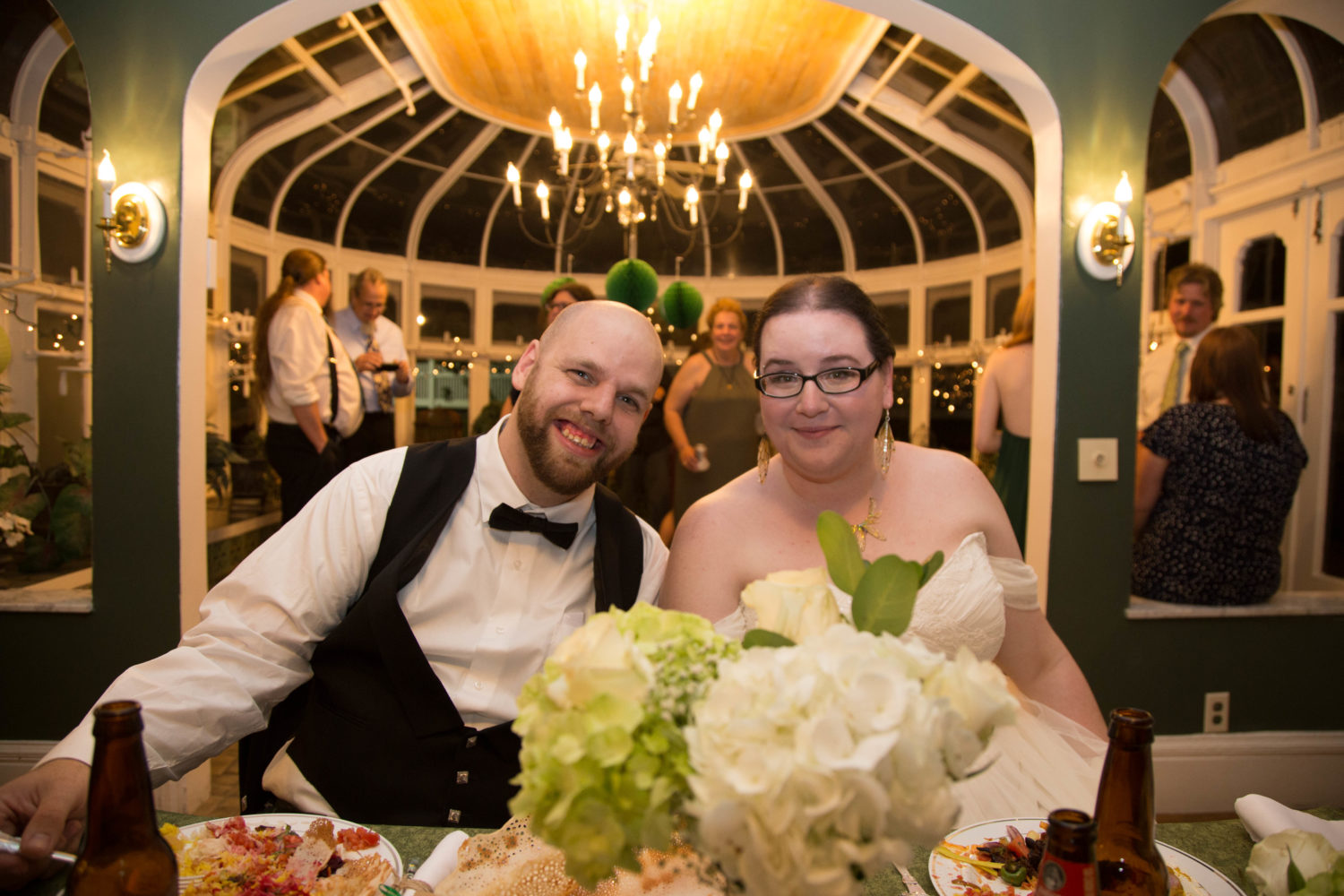 shaina and zach at head table with conservatory in the background