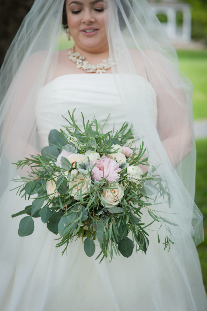 dana in her wedding dress holding a pink and white bouquet